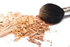 Il bronzer schiacciato della polvere arrossisce e spolverizza la spazzola su fondo bianco Fotografie Stock