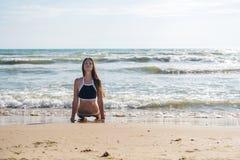 Il bruenette della giovane donna in bikini fa il asana di yoga di Bhujangasana o la posa della cobra sulla spiaggia soleggiata Immagine Stock Libera da Diritti