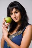 Il brunette con una mela verde Fotografie Stock