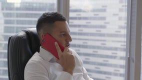 Il bruno piacevole in camicia bianca parla sullo smartphone in ufficio moderno archivi video