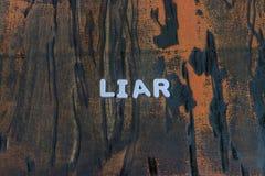 Il bugiardo di parola scritto nei caratteri in grassetto bianchi fotografie stock