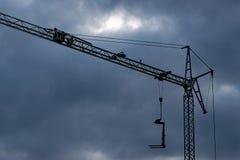 Il buio si rannuvola una gru di costruzione immagine stock