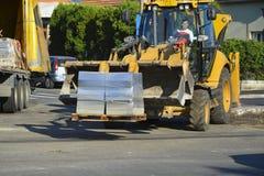 Il bulldozer con il carrello elevatore scarica i bordi concreti Fotografia Stock