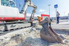 Il bulldozer con il secchio rimuove l'asfalto rotto, fine su Immagini Stock