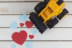 Il bulldozer del giocattolo raccoglie i cuori di carta immagini stock libere da diritti