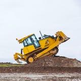 Il bulldozer giallo sporco supera la barriera al suolo fotografia stock