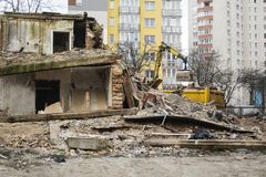 Il bulldozer ha demolito la vecchia costruzione sui precedenti di alloggi nuovi Immagine Stock