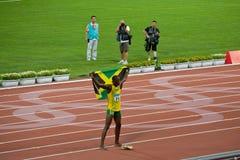 Il bullone di Usain celebra con la bandierina giamaicana Fotografia Stock Libera da Diritti