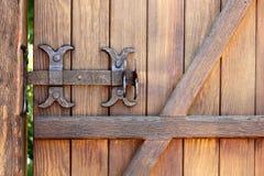 Il bullone forgiato metallo fissa una porta di legno Fotografia Stock