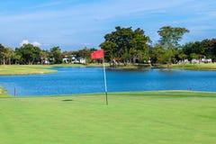 Il bunker della sabbia e della bandiera rossa al bello campo da golf nel lago parteggia al tramonto Immagini Stock