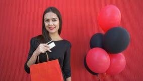 Il buon affare nella vendita stagionale, donna del cliente bacia la carta di plastica e gode degli sconti a venerdì nero con gli  stock footage