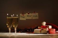 Il buon anno firma dentro il fuoco La composizione dei vetri di champagne, delle ghirlande d'ardore e dei regali di Natale Fotografie Stock Libere da Diritti