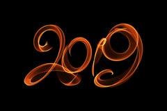 Il buon anno 2019 ha isolato l'iscrizione di numeri scritta con la fiamma o il fumo del fuoco su fondo nero fotografia stock libera da diritti
