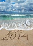 Il buon anno 2014 lava via il concetto 2013 sulla spiaggia del mare Immagini Stock Libere da Diritti