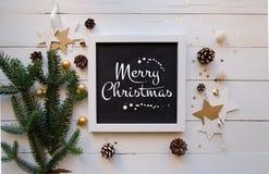 Il Buon Natale che segna il Natale con lettere gioca sui rami di un albero di Natale con i coni Immagine Stock Libera da Diritti