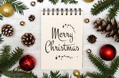 Il Buon Natale che segna il Natale con lettere gioca sui rami di un albero di Natale con i coni Fotografia Stock