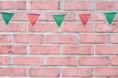 Il Buon Natale fa festa la stamina delle bandiere che appende sul fondo d'annata del muro di mattoni di rosa pastello sull'evento Fotografie Stock