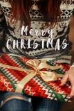Il Buon Natale manda un sms al saluto del segno sulla donna in maglioni con il dee Immagini Stock Libere da Diritti