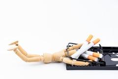 Il burattino di legno ha preso in trappola per topi con le sigarette come esca Nessuno Smo immagine stock