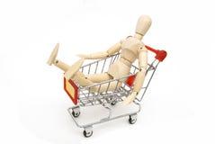 Il burattino si siede in carrello di acquisto Fotografia Stock