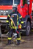 Il burattino tedesco del vigile del fuoco sta vicino ad un'autopompa antincendio su una presentazione immagini stock libere da diritti