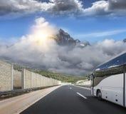 Il bus turistico si precipita lungo la strada principale ad alta velocità del paese contro lo sfondo di un paesaggio della montag Fotografia Stock