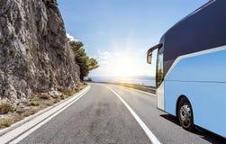 Il bus turistico si precipita lungo la strada principale ad alta velocità del paese contro lo sfondo di un paesaggio della montag Immagine Stock Libera da Diritti