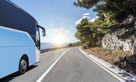 Il bus turistico si precipita lungo la strada principale ad alta velocità del paese contro lo sfondo di un paesaggio della montag Fotografie Stock