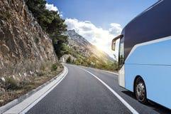 Il bus turistico si precipita lungo la strada principale ad alta velocità del paese contro lo sfondo di un paesaggio della montag Immagini Stock
