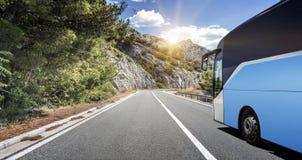 Il bus turistico si precipita lungo la strada principale ad alta velocità del paese contro lo sfondo di un paesaggio della montag Fotografia Stock Libera da Diritti