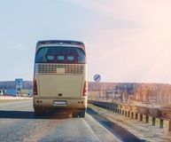 il bus va sulla strada principale in fasci di sole Fotografie Stock