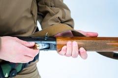 Il cacciatore delle mani del maschio ha inserito il fucile di calibro della cartuccia 12 su un backg Fotografie Stock