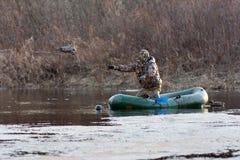 Il cacciatore getta le anatre farcite da un gommone Immagine Stock