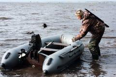 Il cacciatore tira l'imbarcazione a motore Fotografia Stock