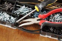 Il cacciavite e le pinze si trovano su una scatola di plastica con molte viti Fotografia Stock