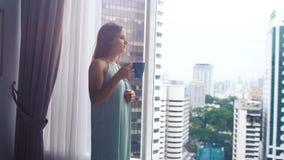 Il caffè bevente della bella giovane donna castana fa una pausa la finestra panoramica con la vista di stupore della città Movime archivi video