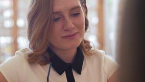 Il caffè bevente della giovane donna e parlare con frien in caffè video d archivio