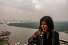 Il caffè bevente di condizione della ragazza sul balcone del condominio ha esaminato il fiume fotografie stock libere da diritti