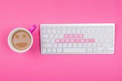 Il caffè con il fronte sorridente ed il buongiorno mandano un sms a sulla tastiera Fotografia Stock Libera da Diritti