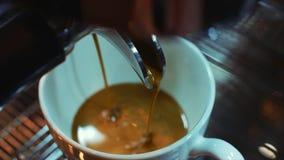 Il caffè del caffè espresso degli italiani più di alta qualità fatti con una macchina professionale del caffè cade in una tazza d video d archivio