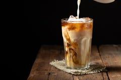 Il caffè di ghiaccio in un vetro alto con crema ha versato più e chicchi di caffè su una vecchia tavola di legno rustica Bevanda  fotografia stock libera da diritti