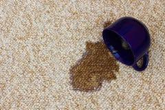 Il caffè ha straripato la tazza sul tappeto fotografia stock
