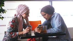 Il caffè musulmano della bevanda di due donne e comunica stock footage