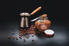 il caffè nero, i fagioli, istante digiuna su un fondo, con i Turchi per fare ed il barattolo di vetro di rapidamente fotografia stock