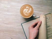 Il caffè sulla tavola di legno con il libro tiene vicino Fotografia Stock Libera da Diritti