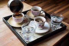 Il caffè turco di versamento è servito con acqua in vassoio fotografia stock libera da diritti