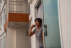 Il caff? bevente di condizione della ragazza sul balcone del condominio ha esaminato il fiume fotografia stock