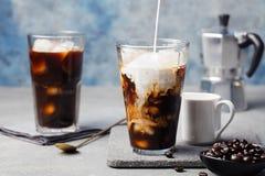 Il caffè di ghiaccio in un vetro alto con crema ha versato più e chicchi di caffè Fotografia Stock