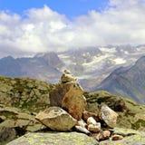 Il cairn del mucchio della roccia indica il modo su un formato del quadrato della montagna Fotografia Stock