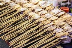 Il calamaro asciutto è perfora dal bastone di bambù nel mercato di strada, Tailandia Fotografie Stock